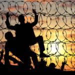 Fluechtlinge versuchen, eine Grenze aus Stacheldraht zu überwinden. Fluechtlinge versuchen, eine Grenze aus Stacheldraht zu überwinden. | Bild (Ausschnitt): © Prazis - Dreamstime.com
