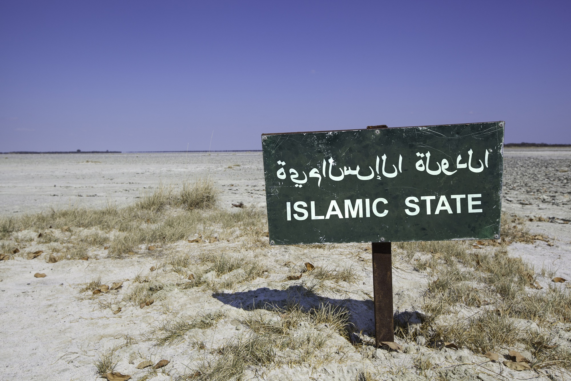 Green sign with the word islamic state in arabic and english language standing in the white sand of the desert.