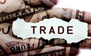 Trade text on a paper scrap over world currency.