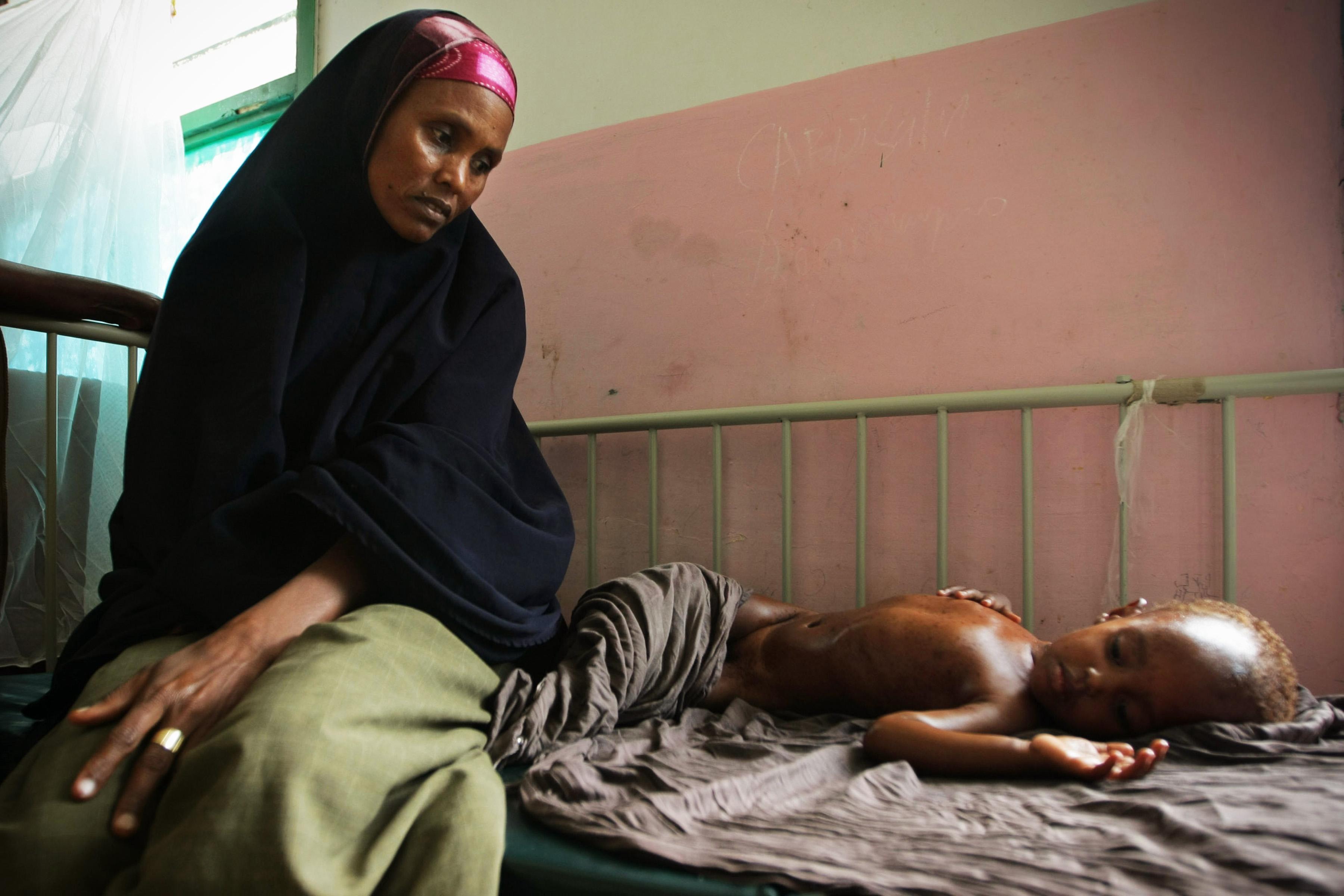 Somalische Mutter wartet in einem Krankenhaus auf Behandlung ihres Kindes. Krankheit und Armut bedingen sich häufig gegenseitig.