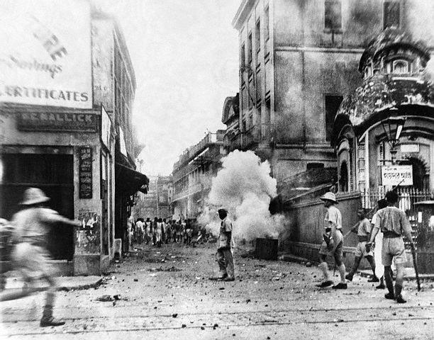 Indische Polizisten setzen Tränengas gegen aufständische Rebellen ein, die einen Hindu-Tempel in Brand stecken wollen (August 1948)