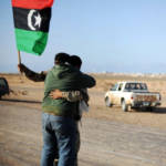 A Libyan rebel holding the old national flag embraces with fellow fighter on March 7, 2011 in Ras Lanuf as opposition forces ceded ground to Moamer Kadhafi's advancing forces, and the United States came under increasing pressure to arm the opposition and the UN appointed a humanitarian envoy. AFP PHOTO/ROBERTO SCHMIDT (Photo credit should read ROBERTO SCHMIDT/AFP/Getty Images)   Bild (Ausschnitt): © BRQ Network [CC BY 2.0] - Flickr
