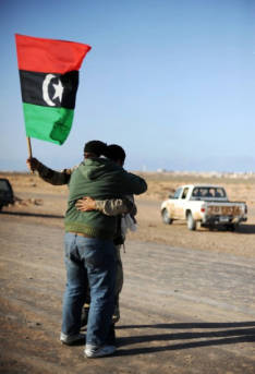 A Libyan rebel holding the old national flag embraces with fellow fighter on March 7, 2011 in Ras Lanuf as opposition forces ceded ground to Moamer Kadhafi's advancing forces, and the United States came under increasing pressure to arm the opposition and the UN appointed a humanitarian envoy.       AFP PHOTO/ROBERTO SCHMIDT (Photo credit should read ROBERTO SCHMIDT/AFP/Getty Images) | Bild: © BRQ Network [CC BY 2.0]  - Flickr