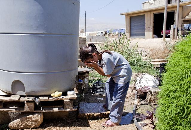 Mädchen in Syrien erfrischt sich an Wassertank