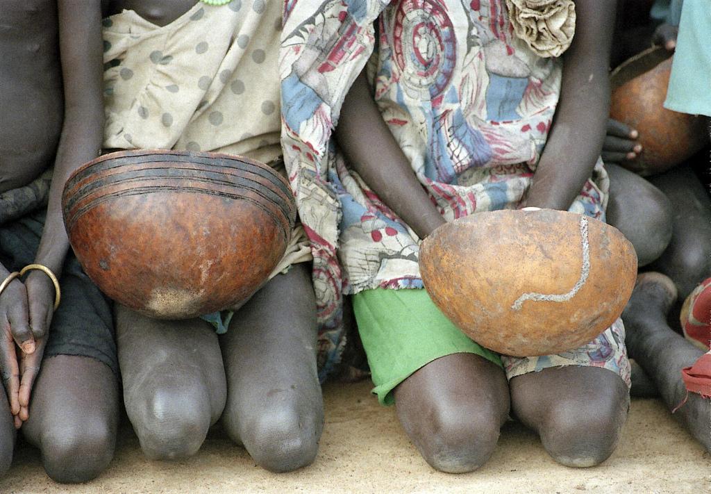 Kinder, die auf die Erlaubnis warten, die verschütteten Körner von World Food Program-Flugzeugen in der Drop-Zone in der Nähe von Thiekthou sammeln zu können.