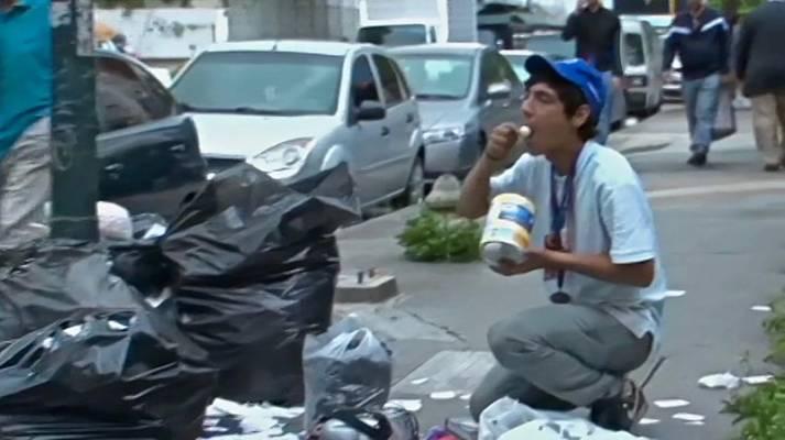 Venezolaner isst von einer Mülltüte Viele Venezolaner können sich keine Nahrungsmittel mehr leisten.     Bild: © Voice of America [Public Domain]  - Wikimedia Commons