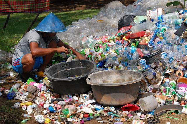 Mann sortiert Plastik