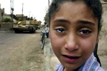 Ein junges irakisches Mädchen weint, als ein britischer Panzer auf das Büro der Baath-Partei zufährt