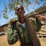 Ein Kämpfer einer Regierungsnahen Miliz steht mit einem Maschinengewehr im ehemaligen Gelände der Flüchtlingskomission der Vereinten Nationen in Somalia | Bild (Ausschnitt): © AMISON Public Information [CC 1.0] - Flickr