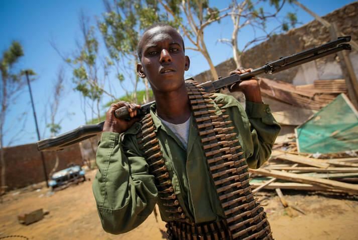 Ein Kämpfer einer Regierungsnahen Miliz steht mit einem Maschinengewehr im ehemaligen Gelände  der Flüchtlingskomission der Vereinten Nationen in Somalia |  Bild: © AMISON Public Information [CC 1.0]  - Flickr