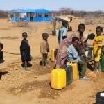 Eine Gruppe von Kindern füllt ihre Wasserkanister in einem Flüchtlingscamp in Burkina Faso auf | Bild (Ausschnitt): © Flickr [CC BY 2.0] - Jean Keberé / Oxfam