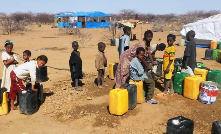 Eine Gruppe von Kindern füllt ihre Wasserkanister in einem Flüchtlingscamp in Burkina Faso auf |  Bild: © Flickr [CC BY 2.0]  - Jean Keberé / Oxfam