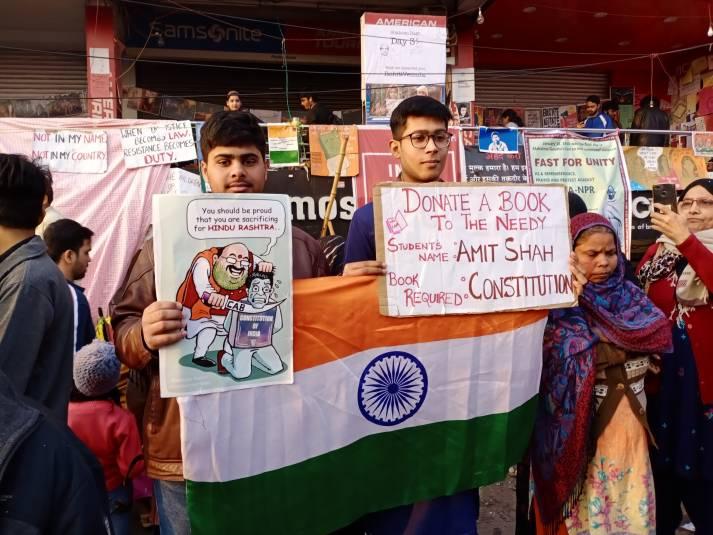 Zwei Inder demonstrieren gegen das neue Staatsbürgergesetz, das in ihren Augen die indische Verfssung verletzt. Ihre Plakate richten sich insbesondere gegen Innenminister Amit Shah, den Initiator der Gesetzesinitiative |  Bild: © DTM [Public Domain]  - Wikimedia Commons
