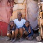 Die Haiti-Domenikanische Philomena Caristil (40), posiert mit ihren Kindern vor ihrer notdürftig zusammengebauten Unterkunft im Flüchtlingslager