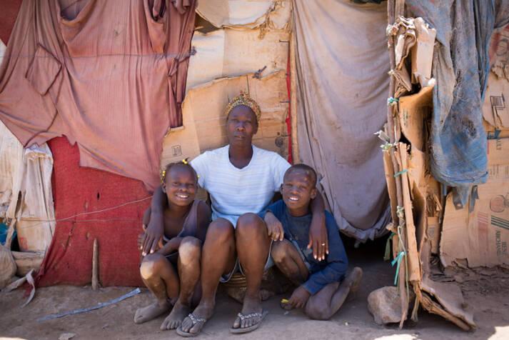 """Die Haiti-Domenikanische Philomena Caristil  (40), posiert mit ihren Kindern vor ihrer notdürftig zusammengebauten Unterkunft im Flüchtlingslager """"Parc Cadeau"""".    Bild: © Fran Afonso [CC BY 2.0]  - flickr"""