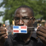 Ein junger Dominikaner haitianischer Abstammung posiert mit der dominikanischen Flagge bei einer Demonstration in Santo Domingo. | Bild (Ausschnitt): © Fran Afonso [CC BY 2.0] - flickr