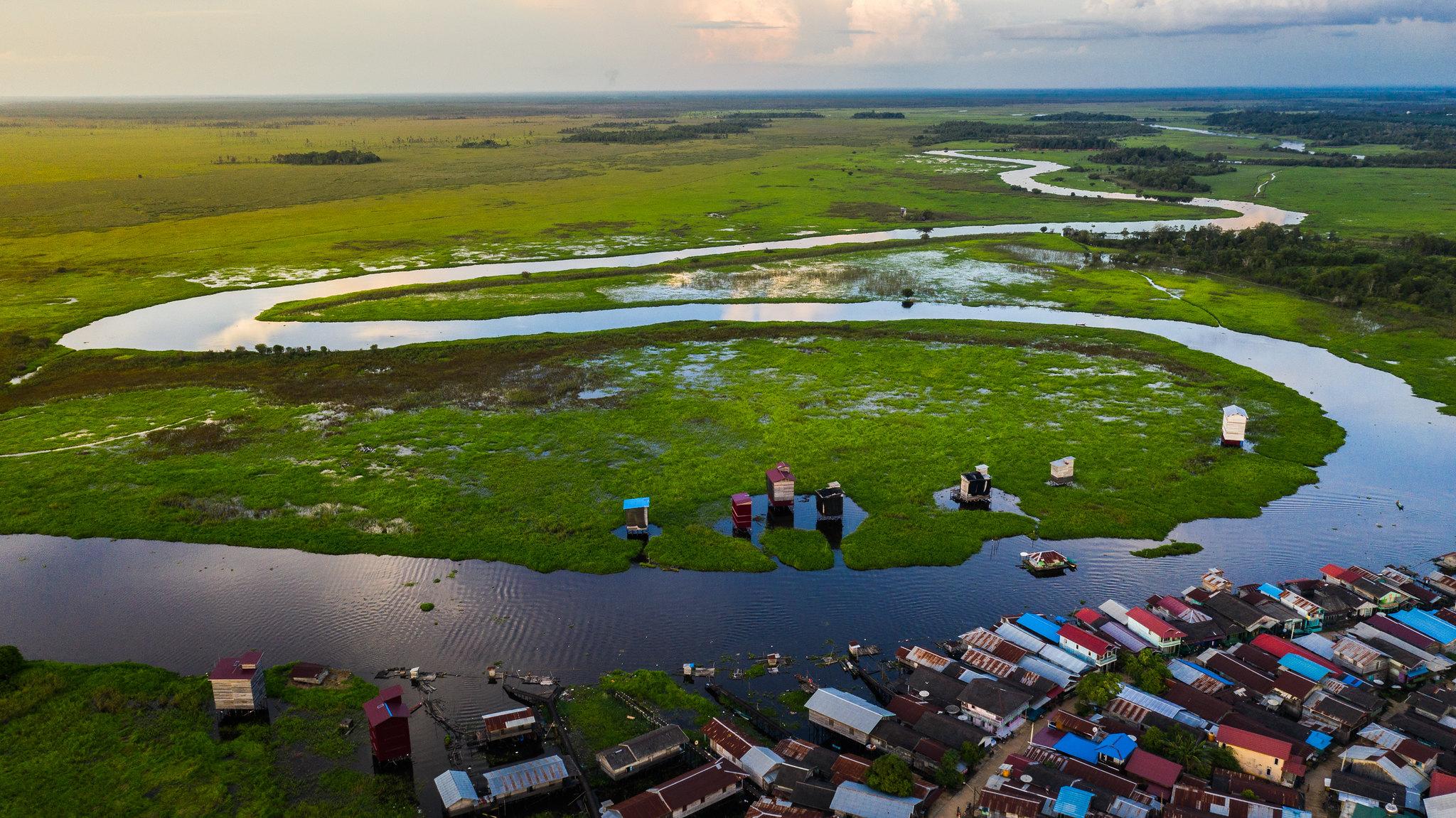 Ein Fluss schlängelt sich durch das Dorf Sabintulung, Kalimantan Timur.