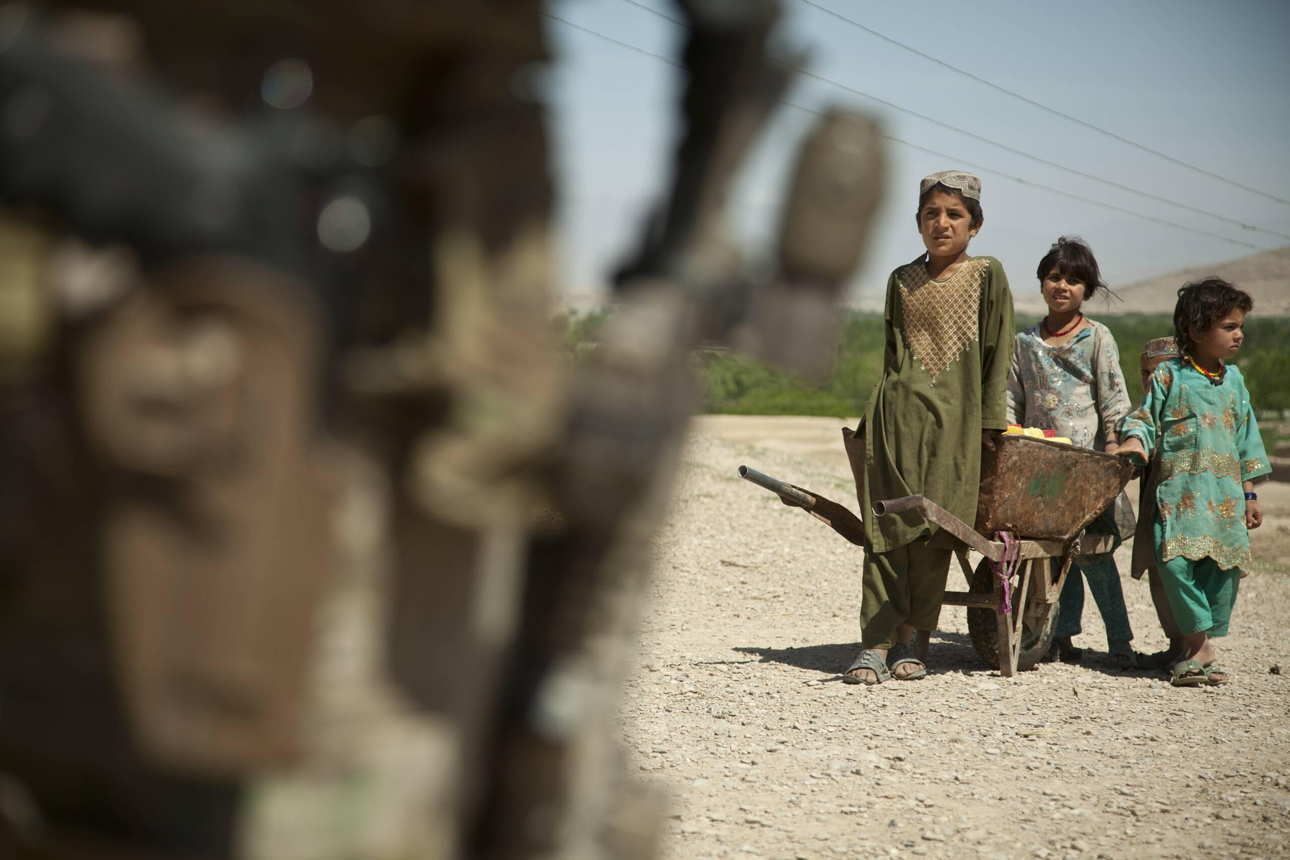 Kinder betrachten einen US-Soldaten auf einem Stützpunkt in Afghanistan