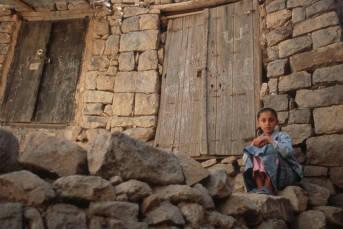 Jemenitisches Mädchen sitzt auf einem Trümmerhaufen
