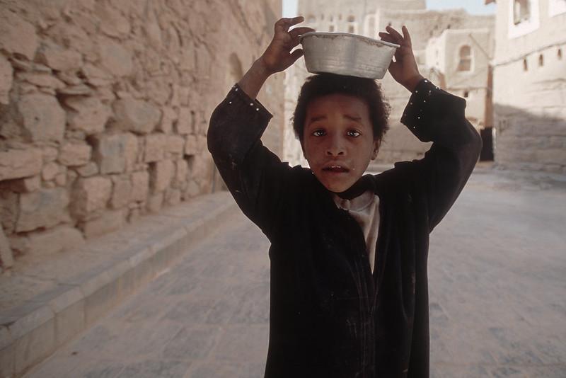 jemenitisches Kind trägt eine Schale auf dem Kopf