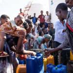 Um eine Wasserstation der UNICEF hat sich eine Menschentraube gebildet. Eine Frau mit ihrem Kind füllt einen Wasserkanister auf. Tigray's Bevölkerung ist von Lebensmittel- und Wasserlieferungen abhängig. Die Hungersnot ist groß. | Bild (Ausschnitt): © UNICEF Ethiopia/2021/Demissew Bizuwerk [CC BY-NC-ND 2.0] - UNICEF Ethiopia / flickr