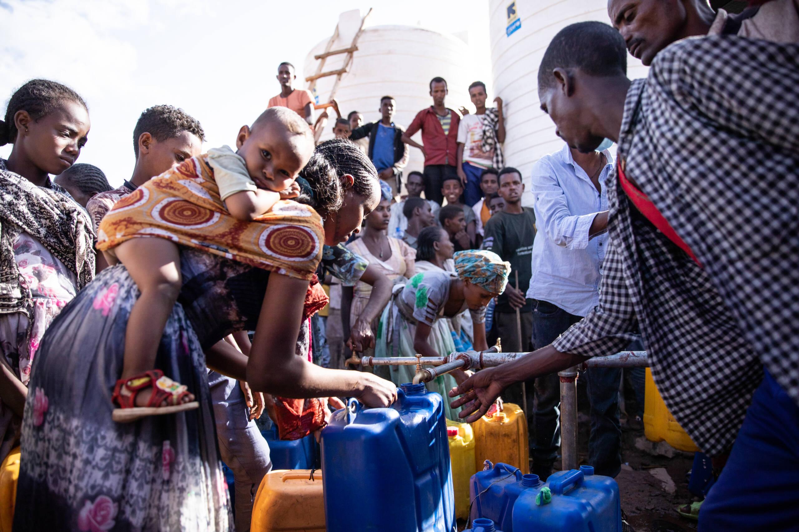 Um eine Wasserstation der UNICEF hat sich eine Menschentraube gebildet. Eine Frau mit ihrem Kind füllt einen Wasserkanister auf.